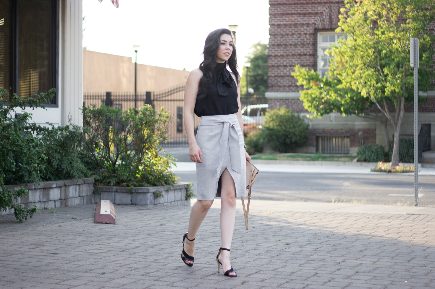 fashion blogger posing in a city, wearing a suede skirt, zara heels, and daniel wellington watch.