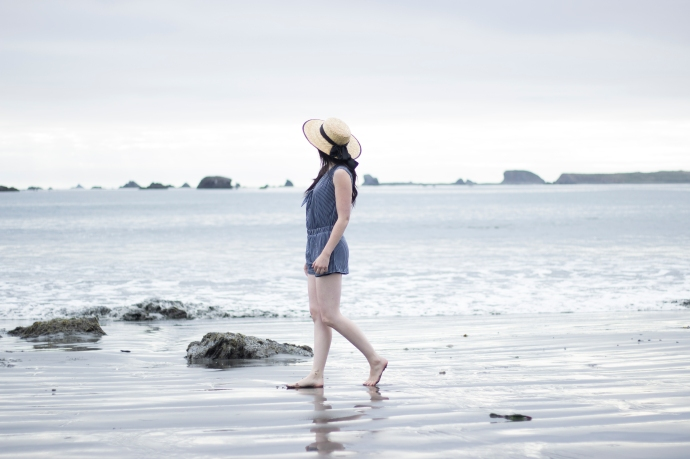 barefoot fashion blogger on the beach. Wearing a romper and a boater hat.