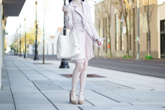 fashion blogger in a city, wearing all pink, pleated skirt, and a Ralph Lauren purse