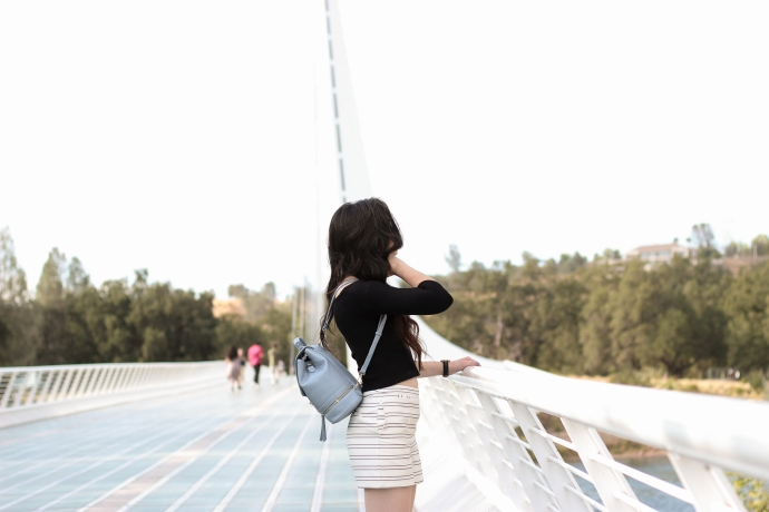 fashion blogger on a white bridge, wearing cat eye Sun Glasses from Marc Jacobs. Wearing striped shorts in summer with a backpack.