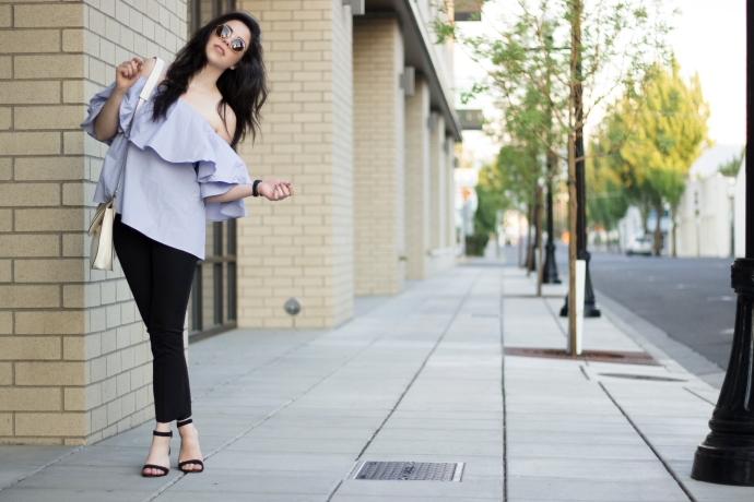 fashion blogger wearing a off shoulder, ruffle top, in a city. Wearing summer clothes and round sunglasses.