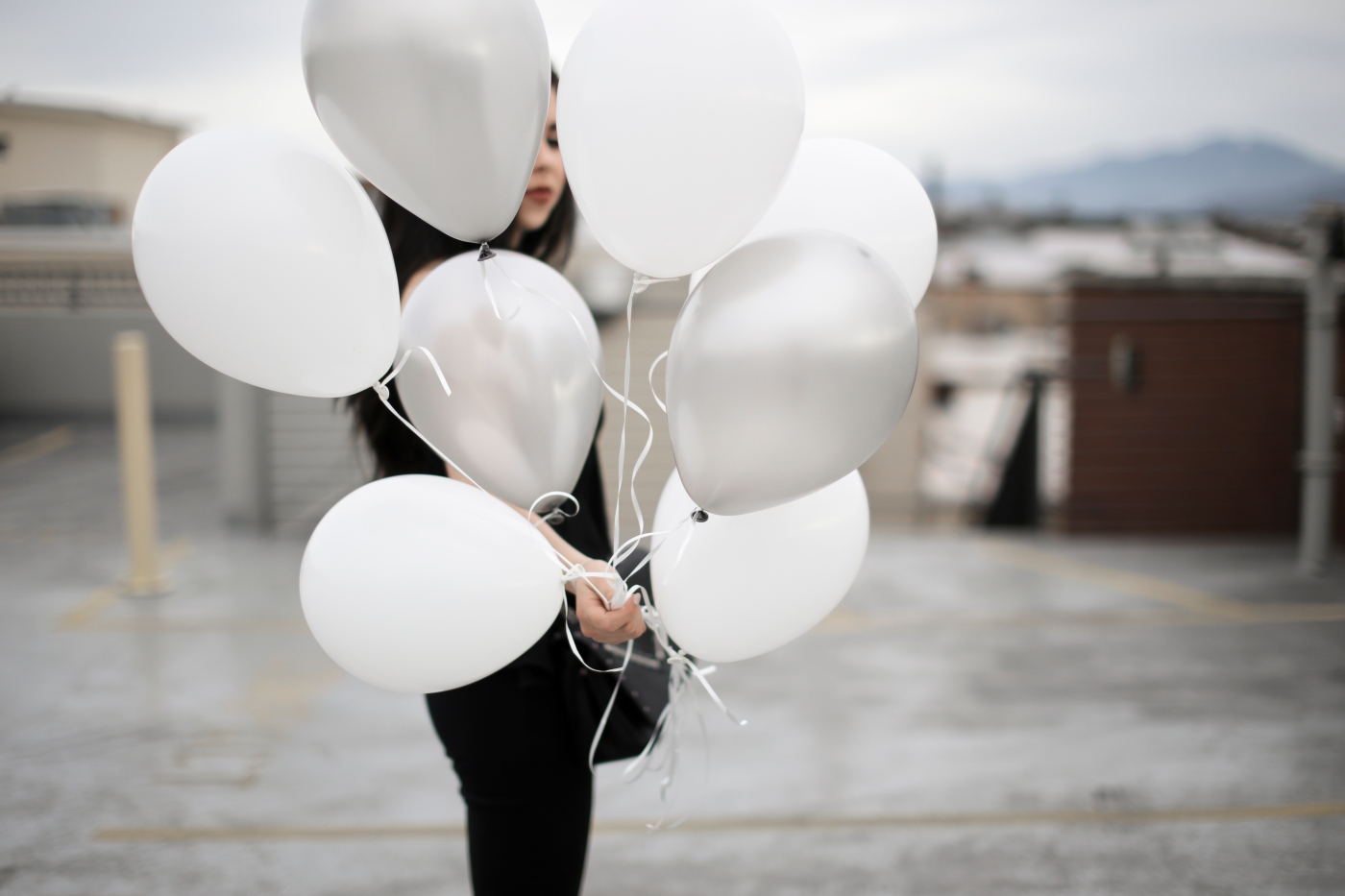 fashion blogger carrying balloons on a parking garage. Wearing black flared jeans, Daniel Wellington watch, and lace up heels.