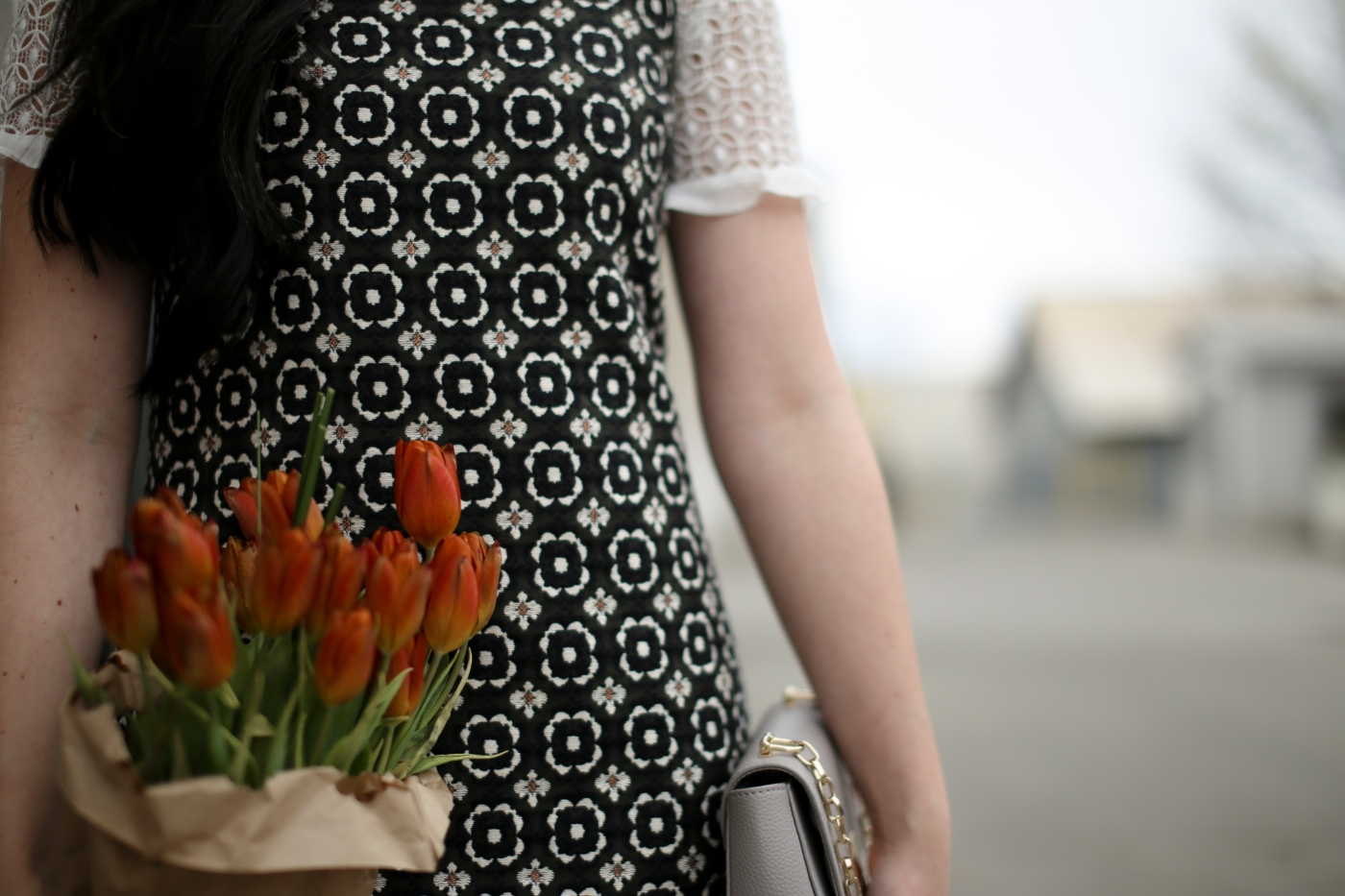 Fashion blogger, wearing a zara lace top, related apparel dress, banana republic shoes, and Bellami hair extensions, and express purse. She is carrying tulips near a warehouse,