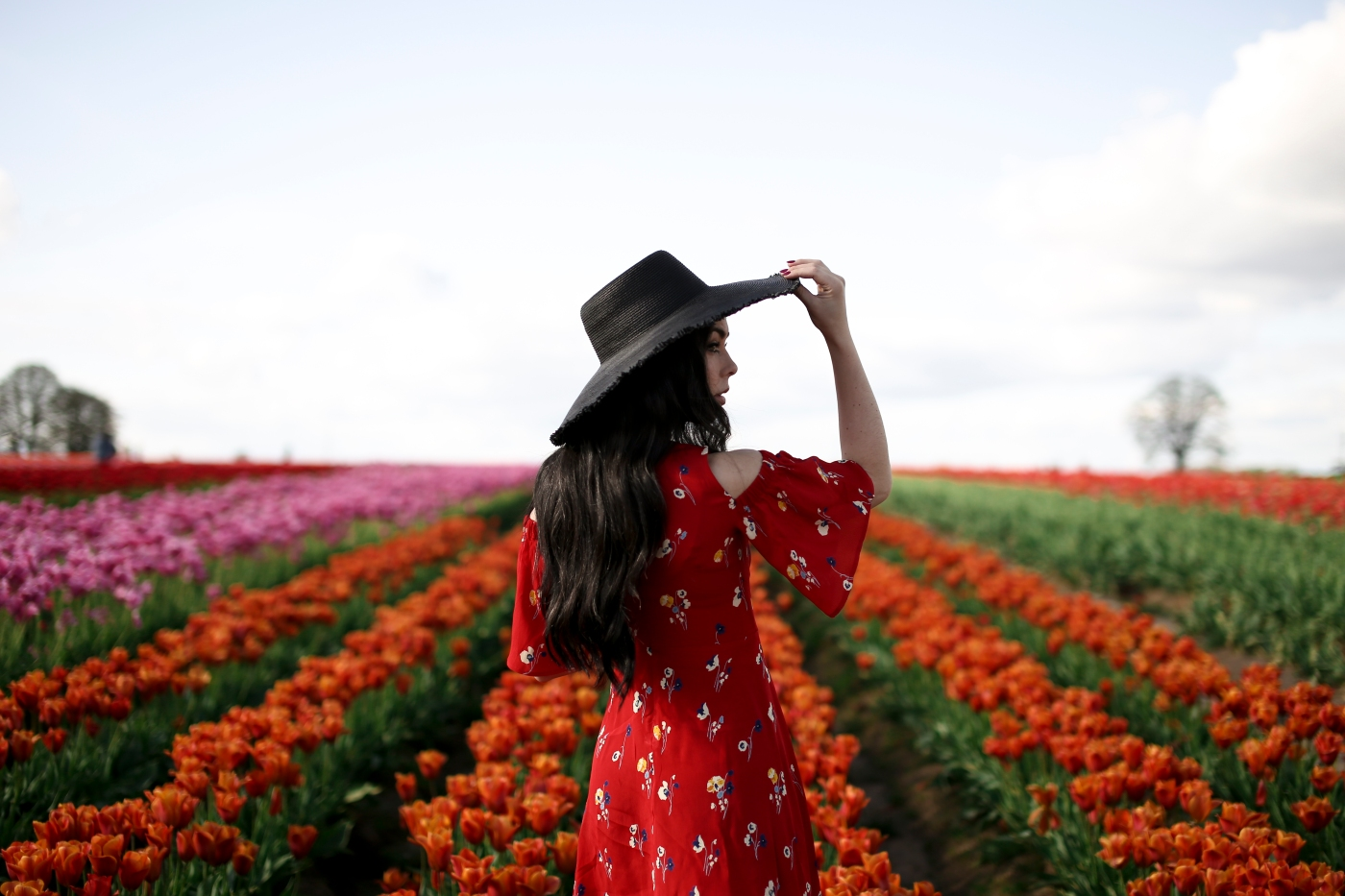 fashion blogger wearing an ASOS ruffle dress, mango straw boater hat, in a field of tulips in Oregon. Wooden shoe tulip festival in Portland.