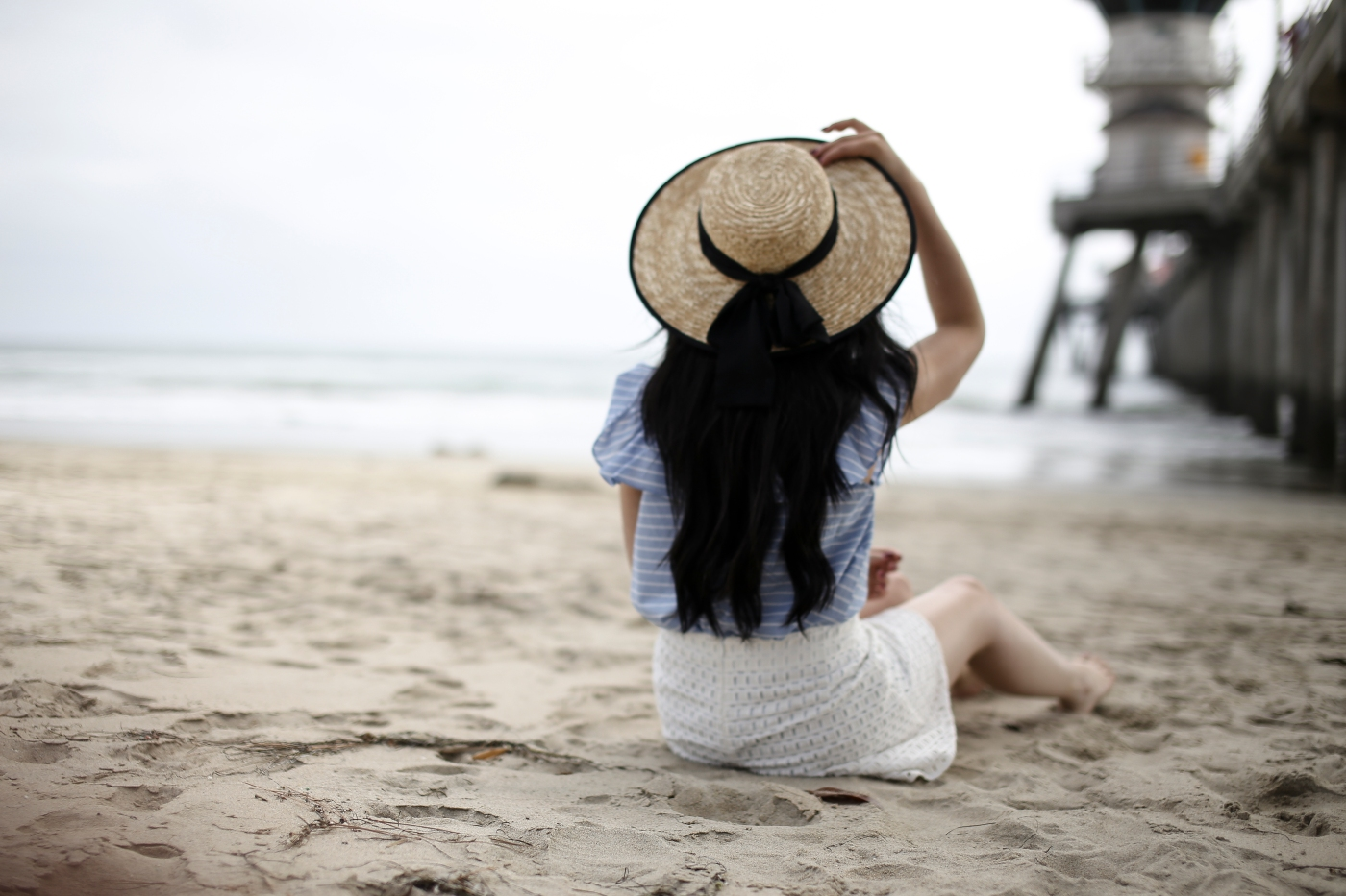 fashion blogger in southern California, walking on a beach barefoot, wearing a Who What Wear blouse, Fashion Bunker White eyelet shorts, and a boater hat. She is wearing Chloe glasses, and mac lipstick